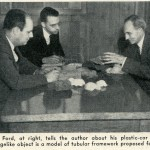 Caption: Henry Ford, at right, tells the author about his plastic-car plans.  The cagelike object is a model of tubular framework proposed for cars.